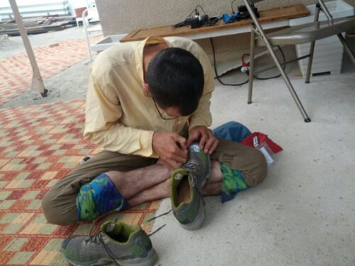 Luke does some duct tape sewing to patch a hole in his shoe